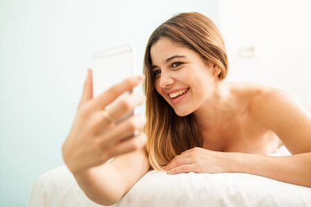 pampered: Portrait of a cute young woman having fun and taking a selfie while getting pampered at a health clinic and spa
