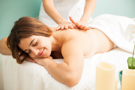 Portrait of a gorgeous happy woman laying on a spa bed and getting a very relaxing massage