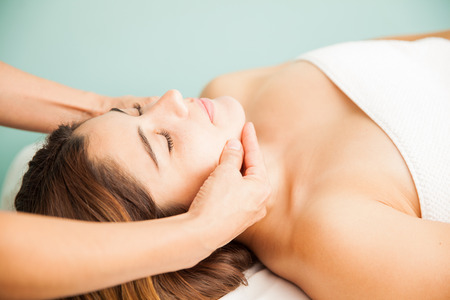 Closeup of a pretty young brunette getting a head massage by the hands of a female therapist at a spa Stock Photo
