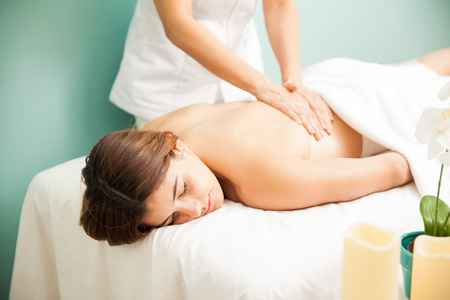 female therapist: Attractive young Hispanic woman getting a back massage from a female therapist at a spa