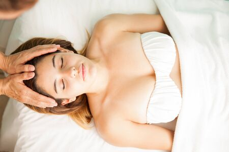 holistic view: Gorgeous young woman laying on a massage bed in the middle of a reiki session at a spa, seen from above Stock Photo