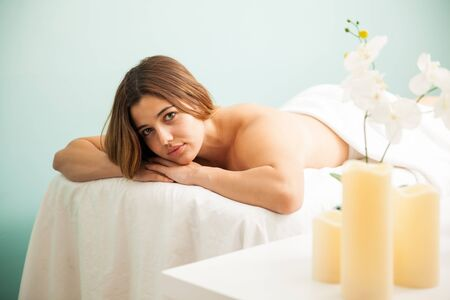 eye contact: Good looking young brunette relaxing on a massage bed at a spa and making eye contact Stock Photo