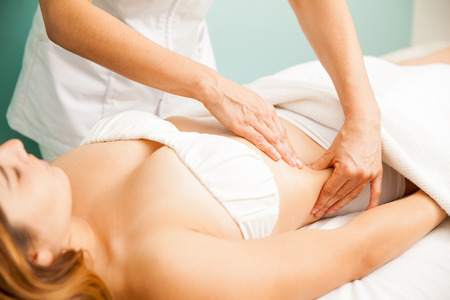 vientre femenino: Hermosa mujer joven que consigue un masaje linfático en un spa de salud y belleza Foto de archivo
