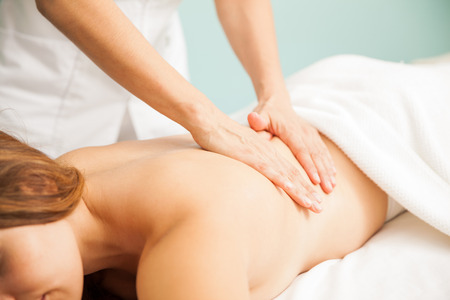 one female: Closeup of the hands of a female therapist giving a back massage to one of her clients