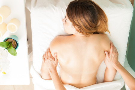 holistic view: Top view of a beautiful young brunette getting a back massage at a health clinic Stock Photo