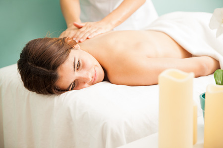 back rub: Pretty young brunette getting a back rub at a health spa and looking very relaxed Stock Photo