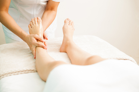 female therapist: Closeup of a female therapist giving a foot massage to a client at a health and beauty spa