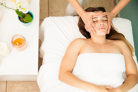 holistic view: Cute young brunette relaxing and getting a head massage by a therapist at a health clinic and spa, seen from above Stock Photo