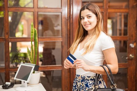cash desk: Portrait of a beautiful young Hispanic woman using a credit card to pay at a cash register in a spa