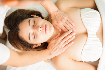 reiki: Top view of an attractive young brunette in the middle of a reiki therapy session with hands over her chest Stock Photo