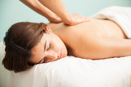 Portrait of a very relaxed young woman with her eyes closed getting a back massage at a wellness center Stock Photo