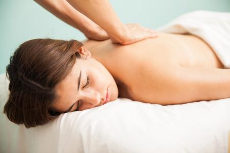 descansando: Retrato de una mujer joven muy relajado con los ojos cerrados recibiendo un masaje posterior en un centro de bienestar