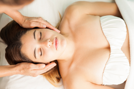holistic view: Top view of a beautiful Hispanic young woman getting her energy balanced in a reiki session at a health clinic and spa