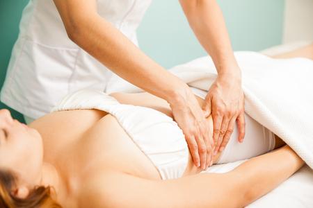 Primo piano delle mani di un terapista che dà un massaggio profondo del tessuto ad un cliente femminile in un centro benessere