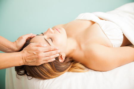 Female therapist balancing energy from a client during a reiki session at a health spa. Both hands on temple Stock Photo