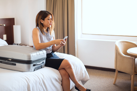 requesting: Pretty businesswoman sitting in a hotel ready to go to the airport and requesting a taxi with her smartphone Stock Photo