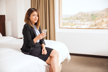 bed skirt: Profile view of a pretty businesswoman sitting on a bed and using a smartphone for work during a business trip