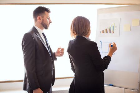 executive women: Profile view of a couple of business partners preparing a presentation and drawing some graphs on a flipchart at a hotel