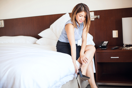 female lawyer: Gorgeous and successful female lawyer getting dressed and putting her shoes in a hotel room during a business trip