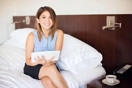 bed skirt: Beautiful young businesswoman using a tablet computer to read the news in the morning during a business trip and smiling Stock Photo