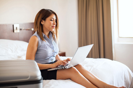bed skirt: Profile view of a cute businesswoman using a laptop computer to send some last minute emails to some clients before leaving her hotel room