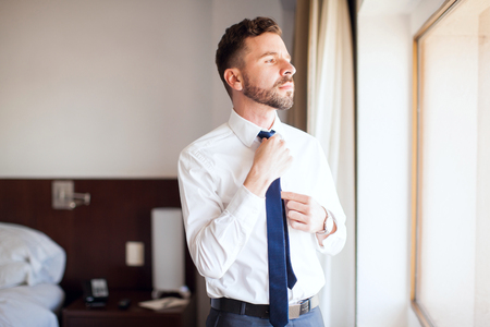 good looking: Good looking young businessman fixing his tie and looking out the window from his hotel room Stock Photo