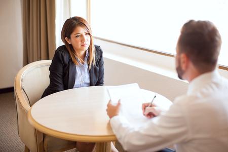 Belle jeune femme portant un costume et parler d'elle lors d'une entrevue d'emploi dans un hôtel Banque d'images - 63064403