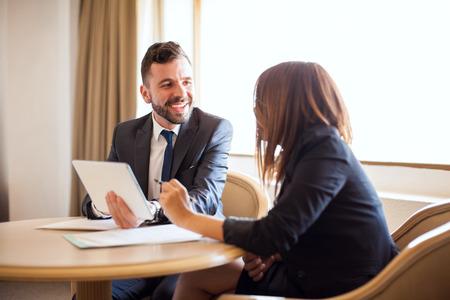 Portret van een jonge zakenman die met een collega flirtert terwijl sommige documenten samen met een tabletcomputer worden bekeken