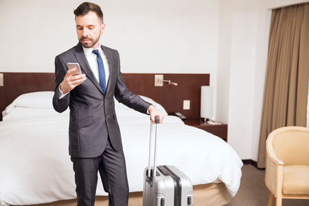 good looking: Good looking young businessman with a beard checking his smartphone during a business trip