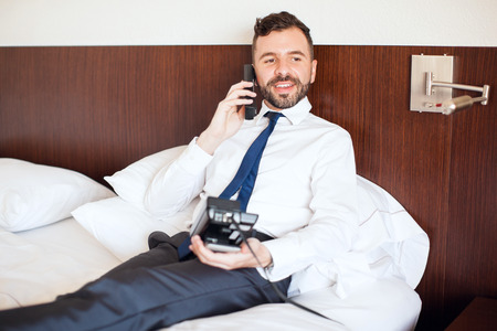 requesting: Handsome young man relaxing in his hotel room and requesting some food and drinks from room service