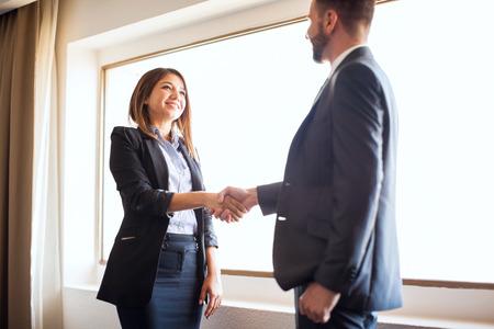 美しいヒスパニック系女性ビジネス マネージャー挨拶し同僚を満たすと揺れが彼と手します。