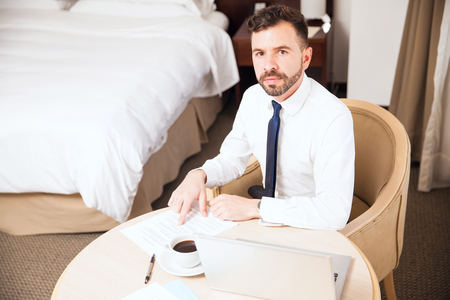 Portrait of a busy young lawyer doing some work and reviewing some documents in a hotel room during a business trip Stock Photo