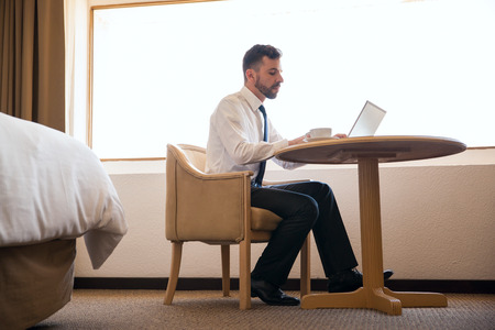 hotel room: Full length view of a busy young manager working on a hotel room during a business trip Stock Photo