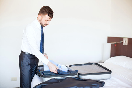 young leave: Good looking young businessman with a beard packing a suitcase and getting ready to leave the hotel