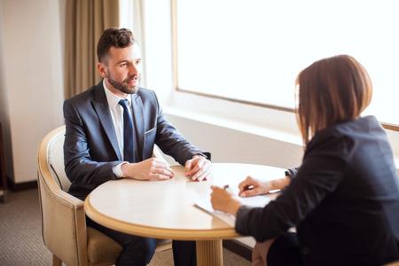 Portret van een knappe jonge zakenman het geven van een verkoopgesprek om een potentiële klant tijdens een bijeenkomst in een hotel