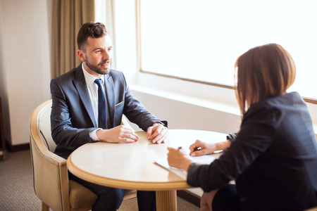 Retrato de un hombre de negocios joven guapo, dando un argumento de venta a un cliente potencial durante una reunión en un hotel Foto de archivo - 63064601