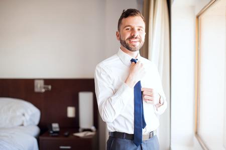 vistiendose: Retrato de un encargado de negocios América vestirse y fijación de su empate temprano en la mañana, durante un viaje de negocios y sonriente