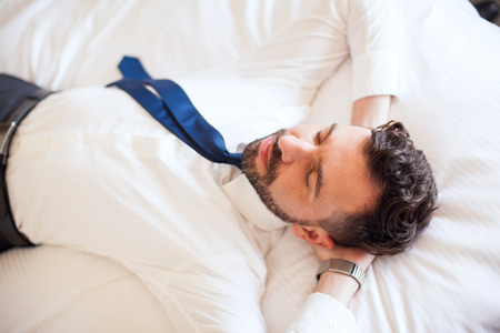 Handsome young businessman lying on a bed in a hotel and relaxing during a business trip