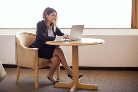 falda: Vista de la longitud completa de una empresaria bastante joven que trabaja en un ordenador portátil mientras está sentado en una habitación de hotel durante un viaje de negocios