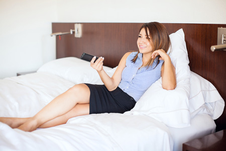 bed skirt: Full length view of a pretty young businesswoman relaxing at her hotel room and watching some TV during a business trip