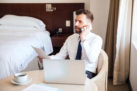 Jonge zakenman die in zijn hotelruimte werkt en aan een cliënt op de telefoon spreekt tijdens een zakenreis Stockfoto