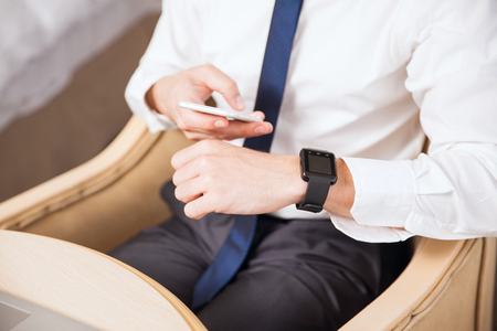 syncing: Closeup of a young businessman wearing a smart watch and syncing it to his smartphone during a business trip Stock Photo