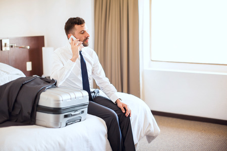Attractive businessman with a beard talking on the phone before leaving the hotel and ending his business trip Stock Photo