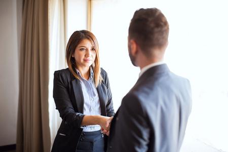 仕事の位置のインタビューの間に女性のリクルーターと握手青年実業家の観点 写真素材 - 63064830