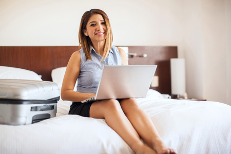 just arrived: Beautiful young businesswoman doing some work on her laptop just as she arrived to her hotel room during a business trip Stock Photo