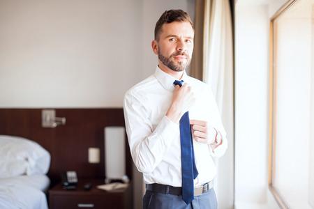 vistiendose: Retrato de un joven abogado de vestirse y poner su lazo en mientras está de pie en una habitación de hotel