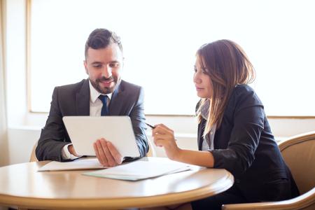 좋은 찾고 젊은 사업가 및 그녀의 비즈니스 파트너 태블릿 컴퓨터 및 일부 문서 작업