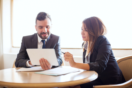 Good looking young businesswoman and her business partner working with a tablet computer and some documents