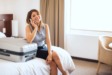 travel woman: Portrait of a beautiful Hispanic young businesswoman talking on a smartphone before finishing her business trip