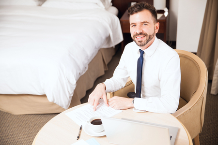 telecommuting: Happy young Hispanic sales representative doing some work in his hotel room and enjoying a business trip Stock Photo